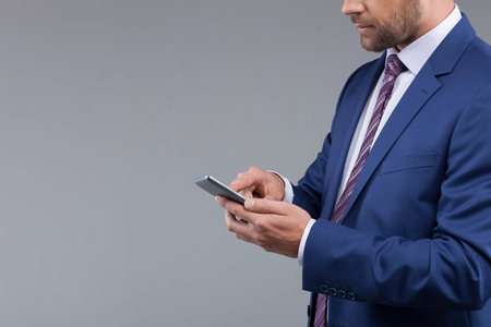 seriousness: Waist up portrait of successful young businessman is holding a mobile phone. He is standing and messaging with seriousness
