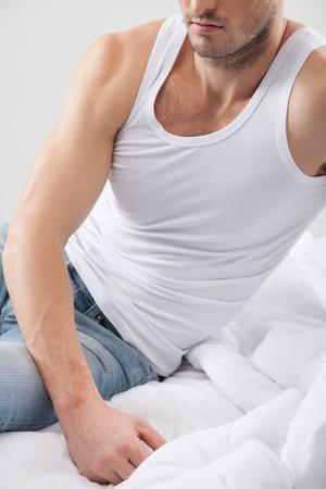 sexualidad: Individuo atractivo ajuste está expresando su sexualidad. Está sentado en la cama en su casa con la relajación