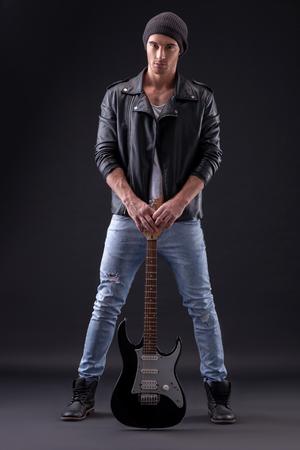 musico: retrato de cuerpo entero del guitarrista joven y atractiva que sostiene la guitarra cerca de sus piernas. Él está de pie y mirando hacia delante en serio. Aislado