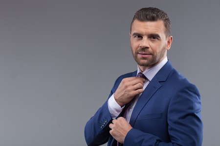 seriousness skill: Waist up portrait of attractive young businessman adjusting his tie before an appointment. He is standing and looking at camera with seriousness.