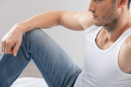 seriousness: Handsome young man is sitting on bed with relaxation. He is thinking about something with seriousness