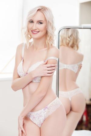 sexualidad: Atractiva joven delgada est� expresando su sexualidad. Ella est� de pie en ropa interior blanca y que presenta cerca de un espejo. Foto de archivo