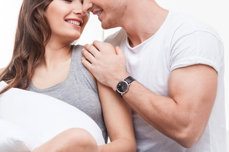 wife: Beautiful young loving couple is sitting and embracing. They are smiling happily. The woman is holding a pillow Stock Photo