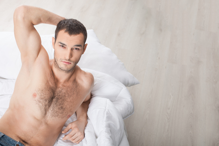 masculinity: Portrait of attractive young man expressing his masculinity and strength. He is lying in bed and looking at camera with temptation. Stock Photo