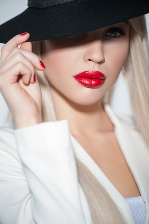 Waist up portrait of attractive blond young woman wearing black hat. She is touching it and looking camera with passion Stock Photo