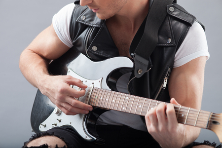 plucking: Close up of arms of cheerful musician playing guitar with pleasure. The man is sitting and plucking the strings. Stock Photo