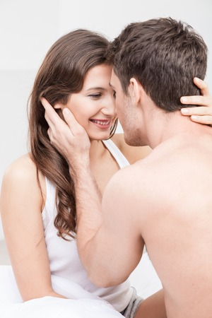 adult young: Attractive young loving couple is relaxing at home. They are sitting on bed and smiling.