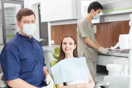 Fröhliche junge Zahnarzt prüft weibliche Zähne. Er ist glücklich in die Kamera schaut. Die Frau auf dem Stuhl sitzt und lächelnd. Der männliche Assistent arbeitet in der Nähe von ihnen mit der Konzentration