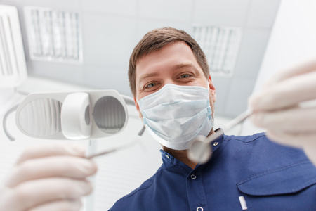 medical man: Experienced dental doctor is standing and showing the medical tools to the camera. He is looking forward happily. The man is wearing a mask and gloves Stock Photo