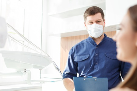 curing: Handsome dentist is standing and holding a folder. He is analyzing the results of curing with concentration. The woman is sitting in chair and smiling. Copy space in left side