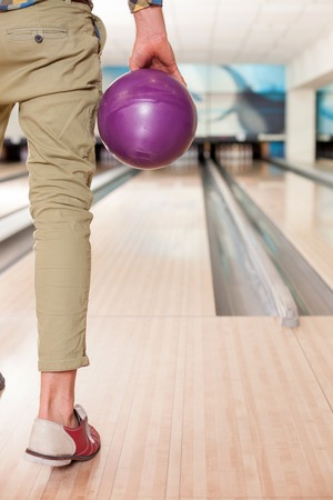 10 fingers: Close up of arm of man ready to throw the bowling ball. He is standing opposite the alley