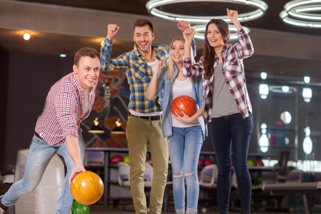 four people: Portrait of attractive man playing bowling with inspiration. He is throwing the ball and looking forward with hope. His friends are supporting him and smiling Stock Photo