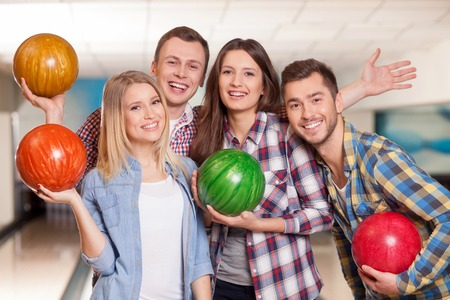 We are happy playing bowling together. Portrait of attractive young friends standing and embracing. They are holding balls and laughing