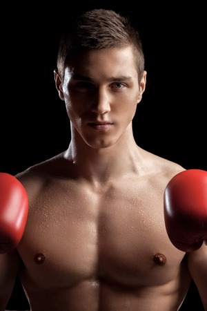 seriousness: Waist up portrait of cheerful boxer standing and fighting. He is looking at the camera with seriousness and raising fists Stock Photo