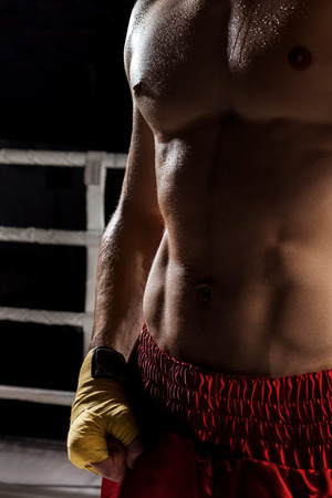 boxing tape: Close up of sweaty trained body of young boxer. He is fighting on the ring with effort