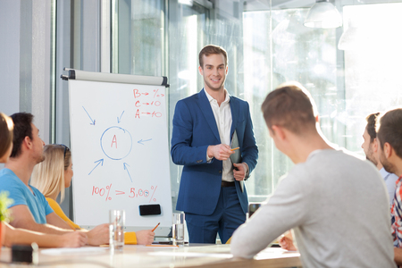 near: Attractive businessman is explaining his ideas in conference hall. He is standing near a whiteboard and smiling. His colleagues are sitting and listening to him attentively