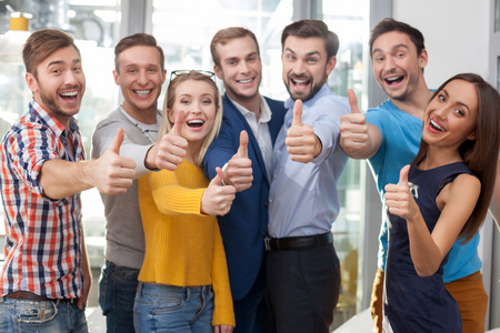Skillful creative team is working with joy. They are standing and giving thumbs up. The men and women are smiling. They are looking at camera happily Stock Photo - 50741714