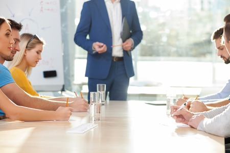 drawing board: Close up of young businessman making a presentation. He is standing is suit. His colleagues are sitting at the table and listening to him attentively Stock Photo