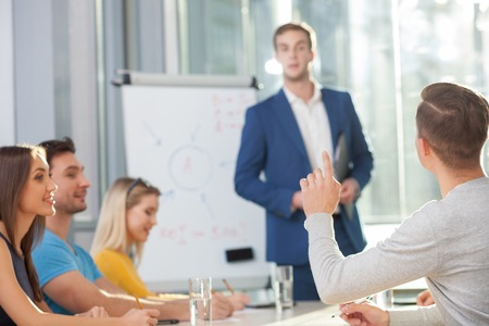colleagues: Skillful young colleagues are taking part is conference. They are sitting at the table and smiling. The businessman is standing near the board. Another man is asking him something