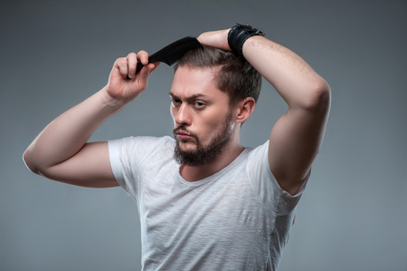 challenging sex: Handsome man is combing his hair carefully. He is looking aside with seriousness. Isolated on grey background Stock Photo