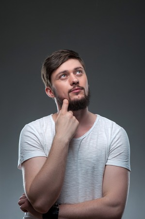 dreamlike: Handsome man is looking up dreamingly. He is touching his beard with his finger. The man is pensive and dreamlike. Isolated on grey background