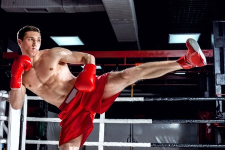 semi dress: Portrait of attractive young boxer training on the ring. He is standing and raising his leg. The man is looking forward with confidence Stock Photo