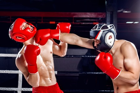 Professional young fighters are boxing on the ring. On man is standing and hitting his opponent with aggression