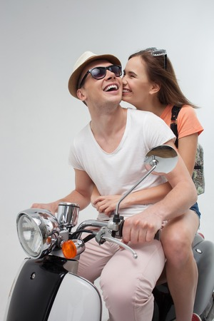 gentleness: I love you. Portrait of pretty young loving couple sitting on scooter. The woman is kissing male cheek with gentleness and smiling. Isolated