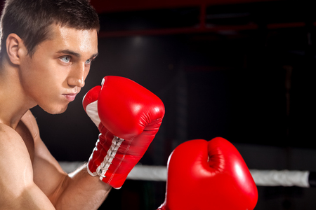 semi dress: Waist up portrait of handsome young boxer boxing with someone on the ring. He is standing and posing. The man is looking forward with concentration