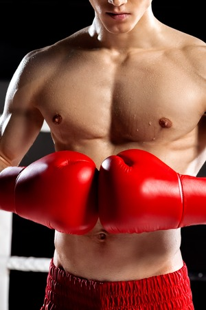 semi dress: Cheerful young boxer is ready to fight on the ring. He is standing and joining fists together with confidence. The man is sweating