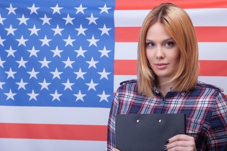 自分の国を誇りに思う。彼女の愛国心を表現する陽気な若い女性の肖像画。彼女は、立っている、フォルダーを保持します。背景にアメリカ国旗