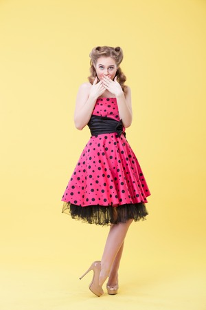 Full Length portrait of pin-up girl raising hands to her mouth with shock. She is looking at camera with interest. The lady is standing in pink dress. Isolated Stock Photo