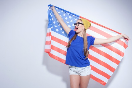 county side: I am very proud of my county. Portrait of beautiful girl standing and carrying usa flag. She is looking aside dreamingly and laughing. Isolated and copy space in left side