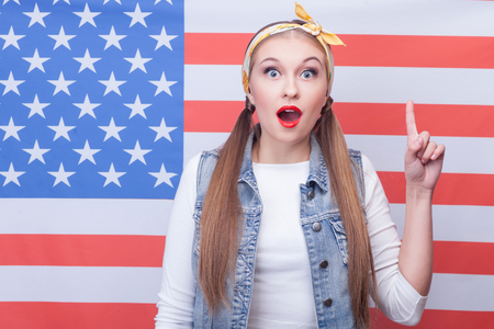 eureka: Eureka. Portrait of beautiful girl pointing finger up pensively. Her mouth and eyes are wide open. She is standing and looking forward with amazement. USA flag on background