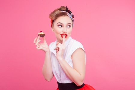 Please do not tell anyone. Portrait of beautiful young woman eating small pie secretly. She is standing and raising finger to her lips. Isolated and copy space in right side