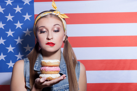 temptation: I want to eat this right now. Waist up portrait of attractive woman holding doughnuts and looking at it with temptation. She is standing near American flag Stock Photo