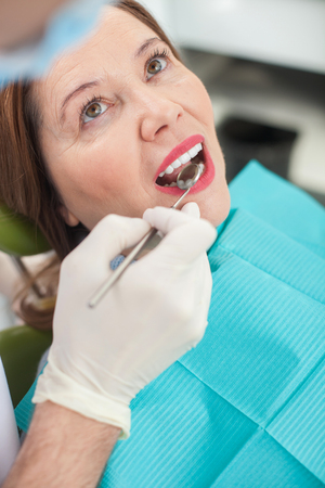 Mature woman is getting dental treatment in clinic. She is sitting and opening her mouth. The dentist is holding tool