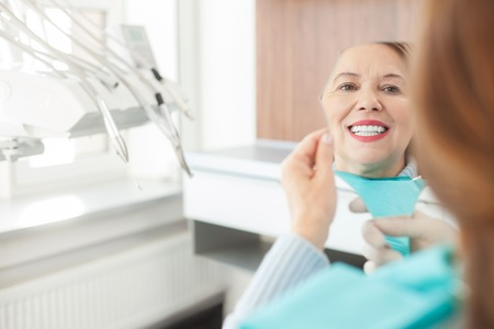 Pretty senior woman is visiting her dentist. She is holding a mirror and looking at her teeth with joy. The woman is smiling happily