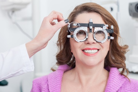 shortsighted: Close up of arm of experienced oculist is using trial frame for lens determination. The middle-aged woman is sitting and looking through this eyewear. She is smiling Stock Photo