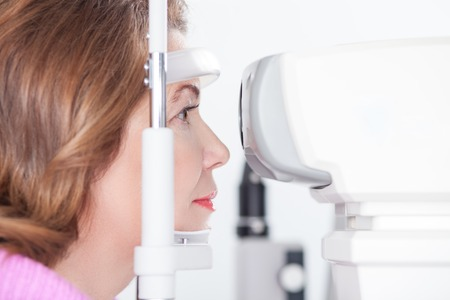 slit: Middle aged woman is having eye examination at the slit lamp in clinic Stock Photo