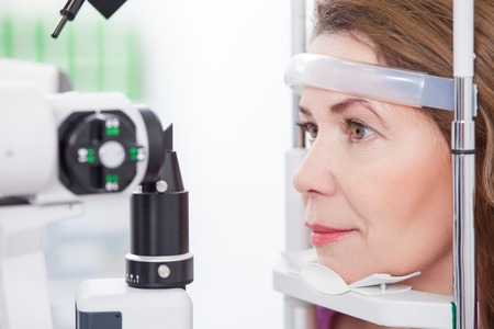 Cheerful woman is having eye examination at the slit lamp in optometrist lap Stok Fotoğraf