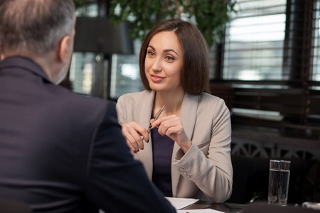 I am ready to sign a contract with you. Attractive young businesswoman is discussing project with her client. She is sitting and holding a pen. The woman is smiling