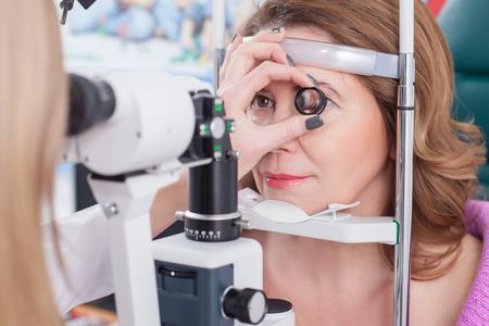 oculista: oculista hábil está examinando ojo femenino con la ayuda de una lámpara de hendidura. Ella es la celebración de la lente cerca del ojo humano. La mujer está sentada y sonriendo suavemente