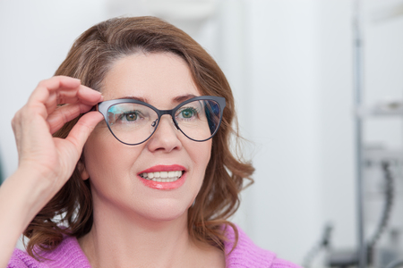 oculist: Cheerful middle-aged woman is wearing new eyeglasses in oculist office. She is looking forward with satisfaction and smiling