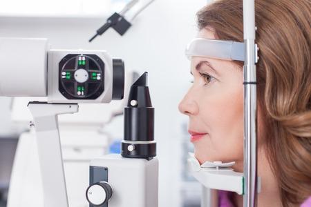 oculista: mujer de mediana edad está mirando en el equipo de prueba del ojo con la concentración. Ella está sentada en el perfil en el laboratorio oculista Foto de archivo