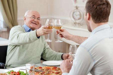 꽤 오래 된 남자와 그의 아들 집에서 와인을 마시는. 그들은 안경을 클릭 하 고 웃 고. 남자들은 테이블에 기쁨으로 앉아있다. 스톡 콘텐츠