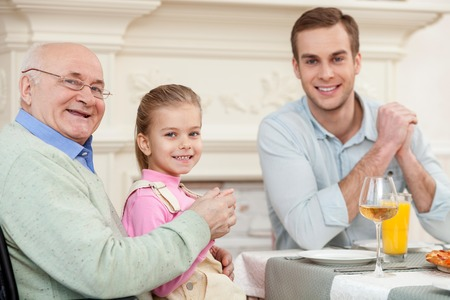 Portrait of cheerful mature grandfather dining with his son and granddaughter. He is holding the girl on his knees. They are looking at camera and smiling