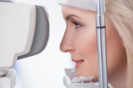 oculist: Alegre chica rubia está mirando en la máquina de prueba del ojo con la concentración en el laboratorio oculista. Ella esta sonriendo