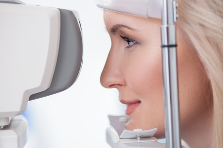 oculist: Cheerful blond girl is looking into eye test machine with concentration in oculist lab. She is smiling