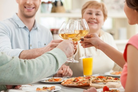 Friendly family is celebrating the event at home. They are clicking glasses and smiling Banco de Imagens
